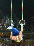 Олимпийский чемпион Eleftherios Petrounias Греции состязается на кольцах ` s людей окончательных на художнической конкуренции гим стоковые фотографии rf