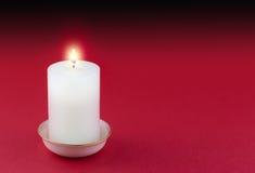 Одиночная освещенная свеча в золоте снабдила ободком белый держатель на красном цвете Стоковое фото RF