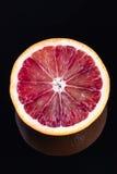 Одиночная половина апельсина крови изолированного на черноте Стоковое Изображение
