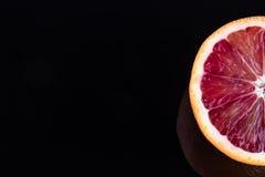 Одиночная половина апельсина крови на черноте Стоковое фото RF