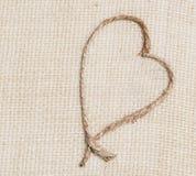 Форма сердца веревочки на tan ткани мешковины Стоковая Фотография