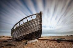 Одиночная шлюпка, который сели на мель на pebbled пляже Dungeness, лачуги England Стоковая Фотография