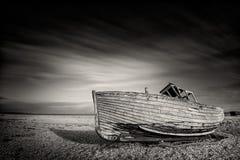 Одиночная шлюпка, который сели на мель на pebbled пляже Dungeness, лачуги England Стоковое Изображение RF
