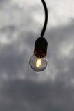 Одиночная электрическая лампочка против облачного неба Стоковые Фото