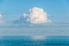 Одиночное облако приостанавливанное в небе над океаном стоковая фотография rf