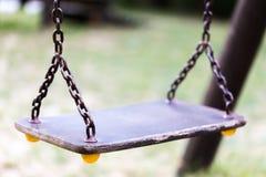 Одиночное пустое старое качание на цепи металла в конце спортивной площадки ребенка Стоковые Фото