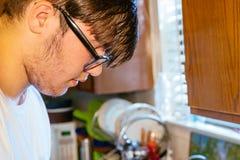 Одиночный домочадец: Молодой человек в кухне стоковая фотография rf
