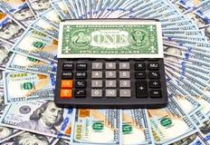 Один американские доллар и калькулятор на предпосылке долларов Стоковое Изображение