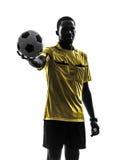 Один африканский рефери человека стоя держащ показывать silhou футбола Стоковая Фотография