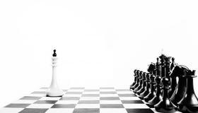 Один белый король шахмат перед враждебной командой драка неравная стоковое фото rf