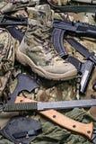 Один ботинок армии и различное оружие Селективный фокус Стоковое Изображение