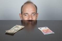 Один глаз смотря доллар и другое на банкнотах евро Стоковые Изображения