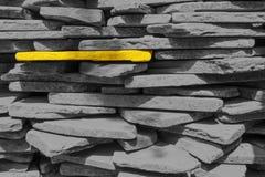 Один желтый камень в стене серого кирпича Стоковое Изображение RF