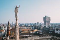 Один из многочисленных di Милана Duomo ststues смотрит на современном городе Стоковое Изображение