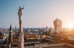 Один из многочисленных di Милана Duomo ststues смотрит на современном городе Стоковые Изображения RF
