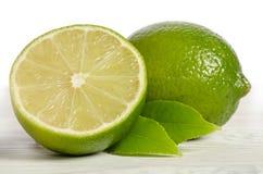 Один лимон с половиной сочной известки на деревянном столе Стоковые Изображения RF