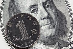 Один китайский юань монетки и 100 долларовых банкнот стоковые фотографии rf