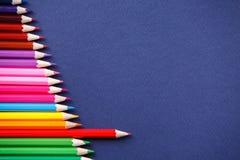 Один красный карандаш стоя вне от серии красочных карандашей На голубой предпосылке стоковое фото rf