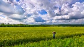 Один просмотр девушки в пшеничном поле с небесами облаков бурными Стоковая Фотография
