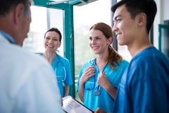 Один другого острословия доктора и хирургов взаимодействуя в коридоре Стоковое фото RF