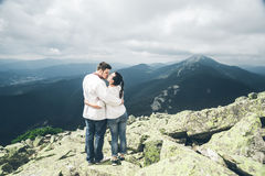 Один другого человека и женщины целуя на верхней части горы Стоковые Фотографии RF
