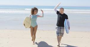 Один другого людей веселя на пляже Стоковая Фотография