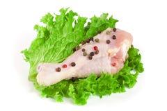 Один сырцовый drumstick цыпленка при лист салата изолированные на белой предпосылке Стоковое Фото