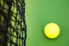Один теннисный мяч на зеленом трудном суде стоковые фото