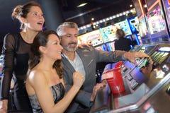 Один человек и 2 девушки играя в азартные игры на казино Стоковые Фото