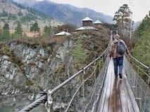 Один человек идет к церков на мосте в горах Стоковая Фотография