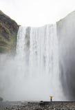 Один человек представляя на водопаде Skogafoss стоковое изображение rf