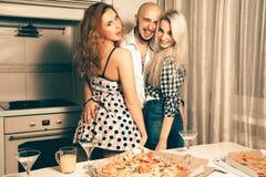 Один человек с смеяться над партии пиццы 2 красивый девушек дома Стоковая Фотография RF