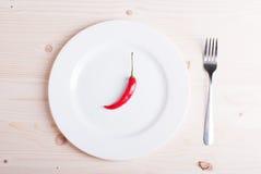 Один чили перца на белой плите около штепсельной вилки на свете wo Стоковое Изображение