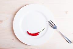 Один чили перца на белой плите около штепсельной вилки на свете wo Стоковое Фото