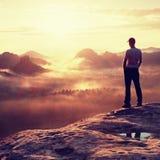 Один hiker в белой рубашке и красная крышка стоят на пике утеса в империях утеса паркуют и наблюдают над туманной и туманной доли Стоковое Фото
