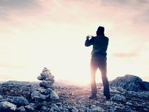 Один hiker принимает фото телефона в горах Человек на горном пике Альпов Взгляд к фиолетовому небу Стоковая Фотография RF