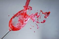 Одичалая брызгая красная жидкость в бокале Стоковые Изображения RF