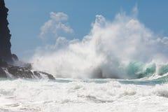 Одичалый, мощный брызгать волны, разбивая на скалистом береге, под bl Стоковое Изображение RF