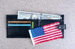 Одна банкнота 100 долларов, черного портмоне и американский флаг Стоковые Фото