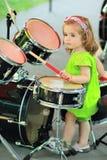 Одна годовалая милая девушка в зеленом romper уча как сыграть барабанчики Стоковые Изображения