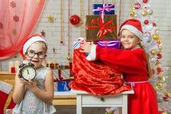 Одна девушка держит вахту с течением времени, 11-55, другое в костюме Санта Клауса обнимая сумку с подарками Стоковое фото RF