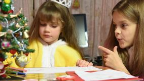 Одна девушка рисует изображение в Новых Годах Eve, другой потехе наблюдая ее видеоматериал