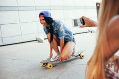 Одна женщина снимая другое на longboard Стоковое фото RF