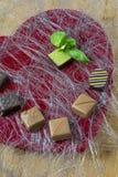 Одна зеленая конфета с некоторыми bonbons шоколада на красной предпосылке формы сердца Стоковое Изображение