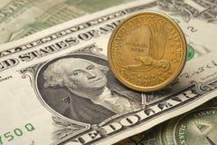 Одна монетка доллара кладя на одну банкноту доллара Стоковая Фотография RF