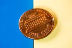 Одна монетка цента в желтой голубой предпосылке Стоковая Фотография