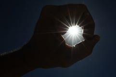 Одна рука улавливая звезды Солнця дальше Стоковые Изображения