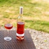 Одна стекло и бутылка красного или розового вина в винограднике осени на деревянной плетеной таблице Время сбора, пикник, тема фе Стоковые Фотографии RF