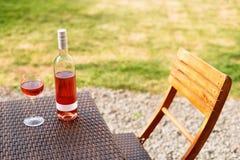 Одна стекло и бутылка красного или розового вина в винограднике осени на деревянной плетеной таблице Время сбора, пикник, тема фе Стоковые Изображения RF