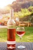 Одна стекло и бутылка красного или розового вина в винограднике осени на деревянной плетеной таблице Время сбора, пикник, тема фе Стоковая Фотография